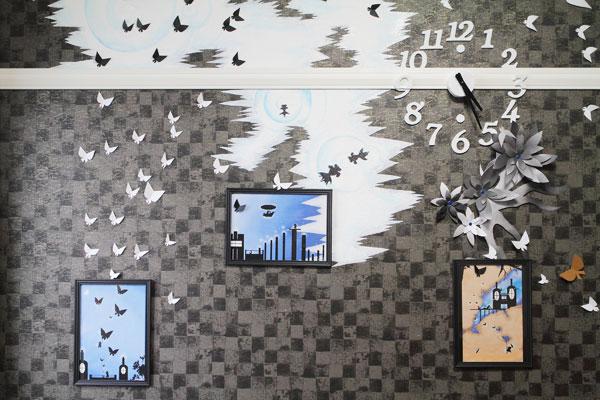 【画像2】壁紙の色味からアイデアを膨らませ、統一感を意識して制作したという壁面。「なんかいまいち……」という友人のアドバイスを受けて、市販の壁時計を手づくりの時計にチェンジ(写真撮影:藤本和成)