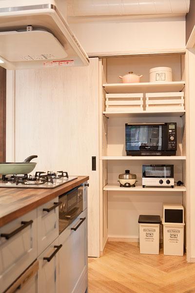 【画像4】キッチン脇には壁面収納。電子レンジやトースターなどの調理家電、ゴミ箱をしまえ、扉をしめれば隠すことができる(写真撮影:片山 貴博)
