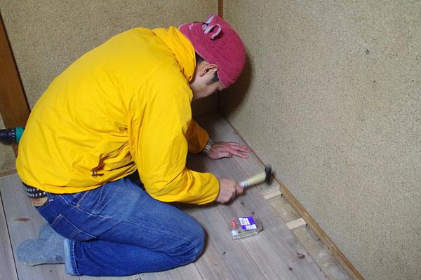 【画像6】最後の一列はどうしても幅が合わないため、床板材をノコギリで切ってはめ込んでいく(写真撮影:玉置豊)