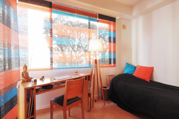 【画像6】こちらは客室、オレンジ&ブルー&ブラック。このスクリーンはIKEAで買い、自分で切ってサイズ合わせしたそう。DIYもお手の物!(写真撮影:藤本和成)