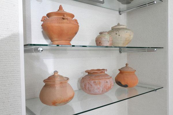 【画像9】リビングルームのオープンシェルフには素焼きのポット類が並ぶ。 「タイの家庭で実際に使われていたポット、すすけている所が良いでしょ」 中に混ぜて日本の陶器も置く、マルチ・カルチャー・ミックスがフランス人らしい(写真撮影:藤本和成)