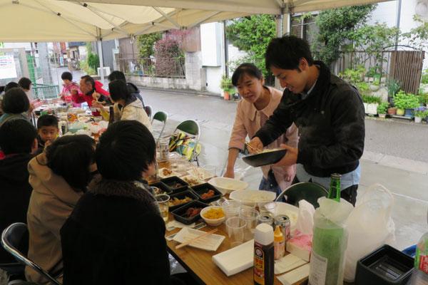 【画像7】バーベキューのシメは大鍋で煮込んだ特製カレー! 持ち寄りのご飯をお裾分けする姿も(写真撮影:末吉 陽子)