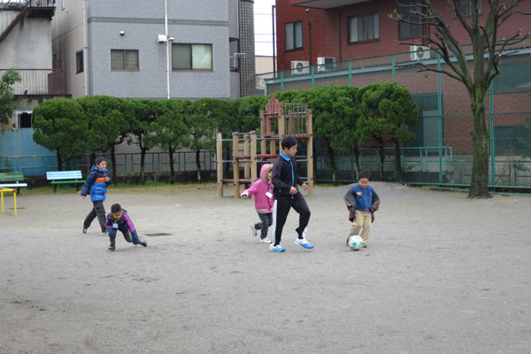 【画像8】学生のころはサッカー部に所属していたという入居者のTさんから、「PARCO CASA」の横にある公園でサッカーを教わる子どもたち。面倒見がいいお兄ちゃんは子どもにとって、うれしい存在です(写真撮影:末吉 陽子)