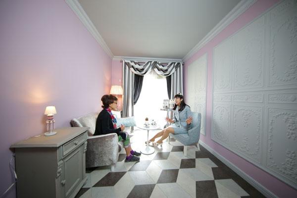 【画像1】ピンク塗り壁の上に貼られた石膏細工のようなデコレーションは、樹脂素材でシート化されたもの。天井回り縁と共に立体的な陰影が生まれ、空間を豊かにしてくれる。 床とカーテンをモダン柄にする事で、甘過ぎないデザインに(写真撮影:本美安浩)