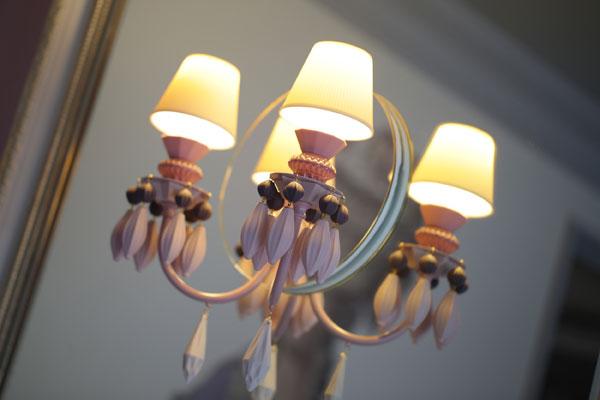 【画像3】陶器のフリンジが付いたリヤドロ社(スペイン)のブラケット照明。製品自体に丸い鏡台が付いた壁付け照明を、更に大判ミラーの上に重ね付けする所がプロ技だ!(写真撮影:本美安浩)