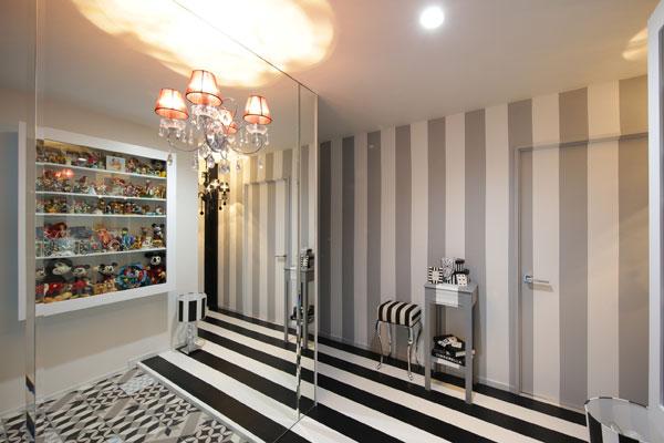 【画像6】玄関の照明も天井ではなく、ミラーにブラケット照明を設置。小さい2灯ものだが、ミラーに映り込んで4灯シャンデリアのよう。 床が映り込んで、かなり広く感じる。錯覚効果、バツグン! (写真撮影:本美安浩)