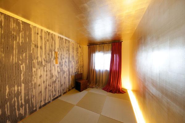 【画像8】天井・壁は金箔の壁紙。左の壁は、'和紙の里'として知られる愛知県小原村の作家による小原和紙。 右の壁下直線に入れたLED照明を調光する事で、金箔の壁が銀色にもなる不思議空間(写真撮影:本美安浩)