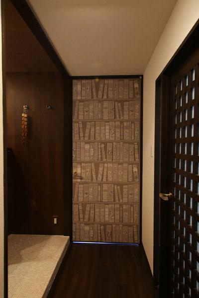 【画像9】ドアに貼られたのは書棚が描かれた壁紙、ブラウンのフローリング・壁にマッチした色調(写真撮影:本美安浩)
