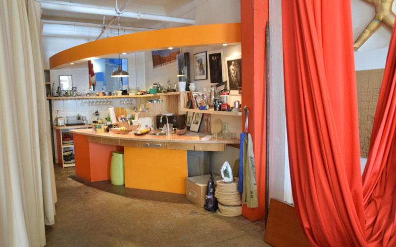 【画像7】リビングから見たキッチン部。キッチンもすべて手づくり。明るいオレンジがポイントだ。引出しの取手はアンティークのフォークだったり細部まで彼の感性が生きる(撮影:小野有理)