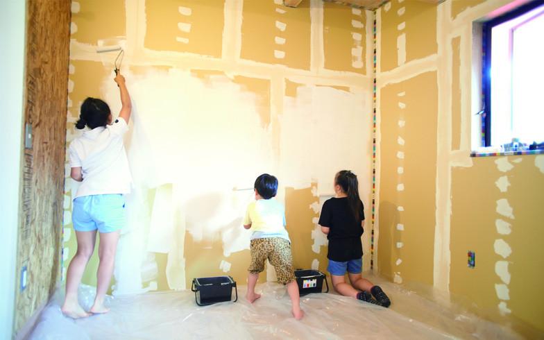 【画像1】まずはホワイトのペンキを壁2面にペイント。子どもたちの塗り方はとても自由!Mさんの長女は「思っていたよりも塗るのってカンタン!」と笑う(写真撮影:橋本裕貴)