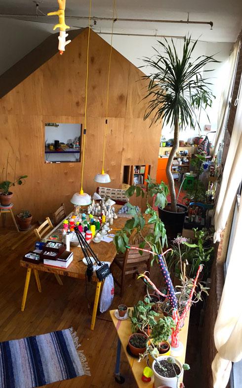 【画像2】寝室にしている小屋から、仕事部屋の小屋を眺める。小屋の間の空間は外と見なしているので、たくさんの木々や植物を置いてアウトサイドな感じを演出している(撮影:小野有理)