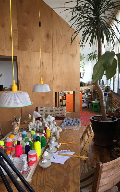 【画像3】リビングから見る小屋。手前のテーブルには展覧会を間近に控え制作真っ最中の次の作品が並ぶ。一面の窓を向いた小屋の前には、たくさんの植物が置かれたプライベートガーデンが。仕事に疲れたらガーデンの椅子に座り外を眺めるのがChiaoのお気に入り(撮影:小野有理)