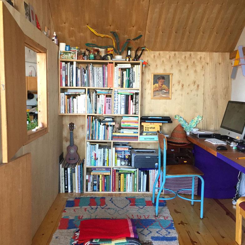 【画像4】友人の手を借りて自作した小屋内部。今はChiaoが仕事に使っている。中の書棚も自分でつくった。開口部(入口と窓)が大きいので、奥まで日射しが届きとても明るい(撮影:小野有理)
