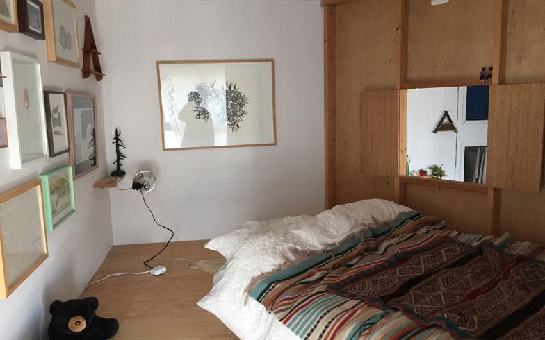 【画像6】ツリーハウス内部。白い壁が光を反射しとても明るい。眠りに集中するために潔く好きな絵だけを置いた。小窓から見降ろすリビングの風景も、視点が変わって気分転換の一つになる(撮影:小野有理)