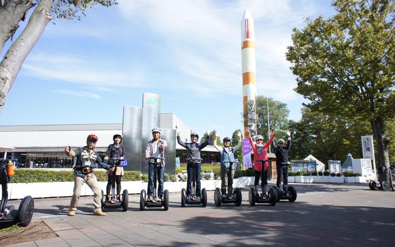 【画像1】つくば市の街めぐりツアー。参加者はカメラを向けると自然と笑顔やバンザイをしてくれるそう(画像提供:セグウェイジャパン)