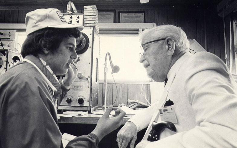【画像2】クレイグ・ウェブ氏(左)が若かりし1972年、あのケンタッキーフライドチキン創業者カーネル・サンダース氏に取材している写真(資料提供:Craig Webb)