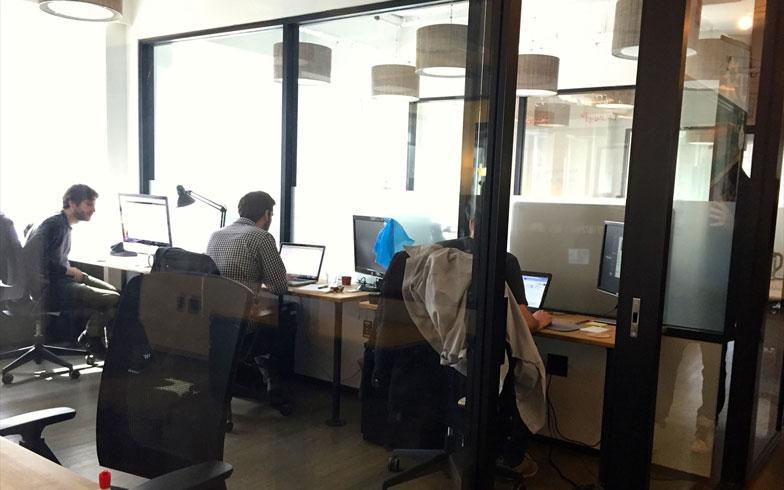 【画像17】スペース貸しの小規模オフィススペース。フリーアドレスのデスクスペースと、ある程度の人数で働けるスペース貸と2種類がある。仕切りはすべてガラスで中が丸見えなのが特徴。でもみんな目隠しをつけたりしないようだ(撮影:小野有理)