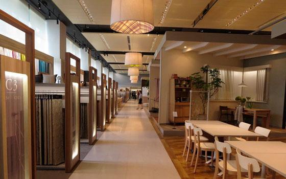 【画像2】壁・床・カーテンの展示ゾーンに分かれ、セミナールームやシミュレーション・システムなども備えた大型ショールーム。左はカーテン展示ゾーン、打ち合わせスペースも充実(写真撮影:藤井繁子)