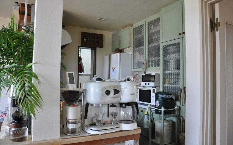 【画像2】リビング側からみたキッチン。奥の緑の棚は自分たちで色を塗り、ガラスはシールで加工。奥の窓上部にあるブレーカーもシールを張って木目調に(写真撮影:嘉屋恭子)