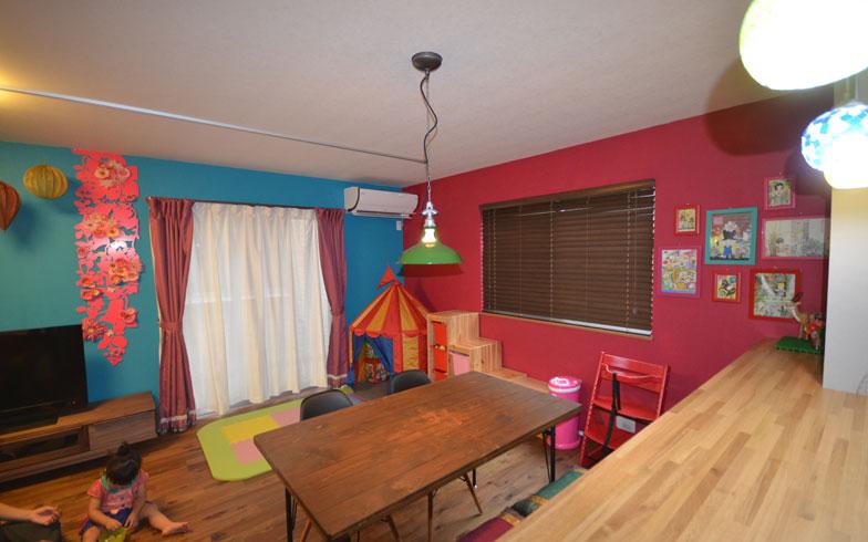 【画像3】変更後。以前住んでいた部屋のイメージを受け継いだ鮮やかなブルーと赤の壁面が印象的。ツヤを抑えた質感のある無垢フローリングに変更。洋室との間仕切り壁を取り払い広々したリビングダイニングに(写真撮影:西村巌)