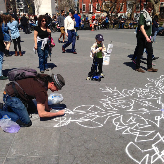 【画像13】道路に10mほどの大きな絵を描いているアーティスト。チョークで描いているので最初に描いた部分は人に踏まれたりして薄くなったり、子どもたちがわざと踏んで遊んだり。それでも一向気に留めず黙々と描き続ける(撮影:小野有理)