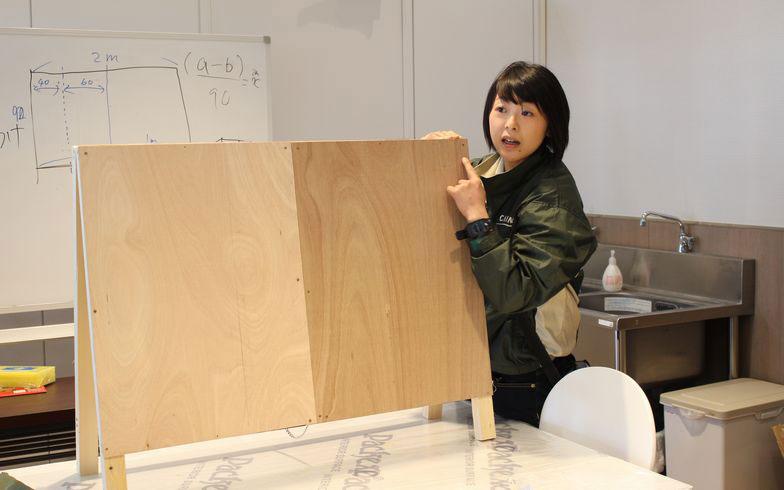 【画像1】木の板を使って壁紙張りとペンキ塗りを行う。講師の関さん(写真撮影:SUUMOジャーナル編集部)