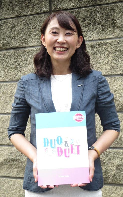【画像1】ヘーベルハウスの二世帯住宅「DUO&DUET」カタログを手に、二世帯住宅研究所の下川さん(写真撮影:藤井繁子)