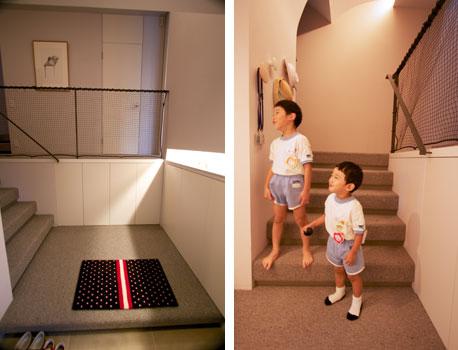 【画像2】玄関ホールと、そこから居室へ続く小階段もすべてカーペット敷き。出迎えてくれたのは幼稚園に通う元気な子どもたち。もうひとり赤ちゃんがいるから、手すりにはネットがはられている(写真撮影:井村幸治)