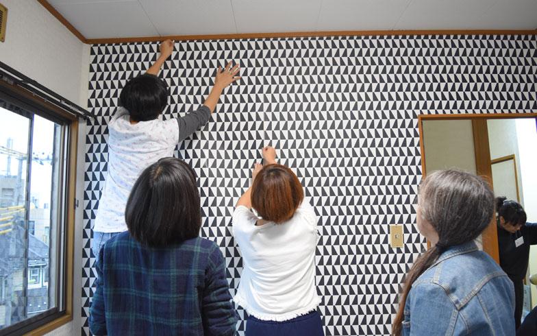 【画像3】壁紙張りの様子。株式会社ジュブリーの輸入壁紙を2部屋で4本使用。「自分ひとりで張れるかも?と思ったけど、脚立にのぼって高い位置で壁紙を手で押さえると、ほかの道具が取れなかったりするから、やっぱり2人以上いたほうがいいね~」などと話しながら、和気あいあいと作業をしていく(写真撮影:SUUMOジャーナル編集部)