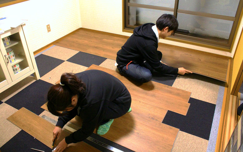 【画像4】床張りの様子。株式会社ナガイの「ウルティモ」を使用。既存の床の上から敷くことができ、接着剤やくぎを使用しないため賃貸でも施工可能。軽い素材で、板と板をパズルのように組み合わせて差し込んでいくだけなので、女性一人でもラクラク。壁を塗る・壁紙を張るよりも簡単だが、これだけでも部屋の雰囲気がガラっと変わる!(画像提供:和光建物株式会社)