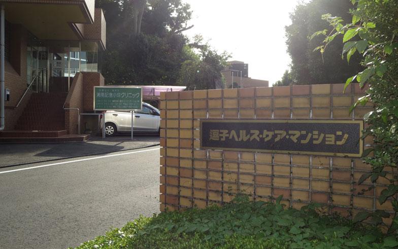 【画像1】JR「鎌倉」「逗子」両駅からバスで15分弱、目の前がバス停の「逗子ヘルス・ケア・マンション」入口。左の建物は同敷地内併設のクリニック(写真撮影:藤井繁子)
