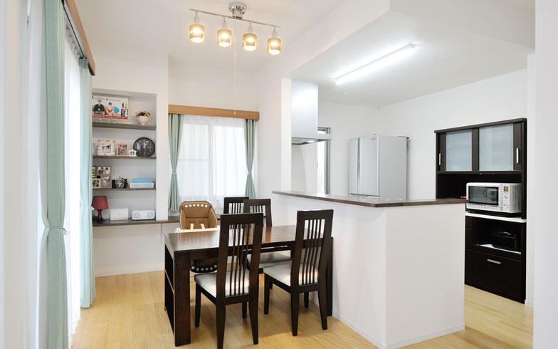 【画像7】ダイニング・キッチン/左奥の飾り棚とテーブル以外、これといった家具は置いていない。キッチンはオープンで使いやすいが、隠したいモノは手元に隠れるので特に来客時には都合が良いそうだ(写真撮影/柴田ひろあき)