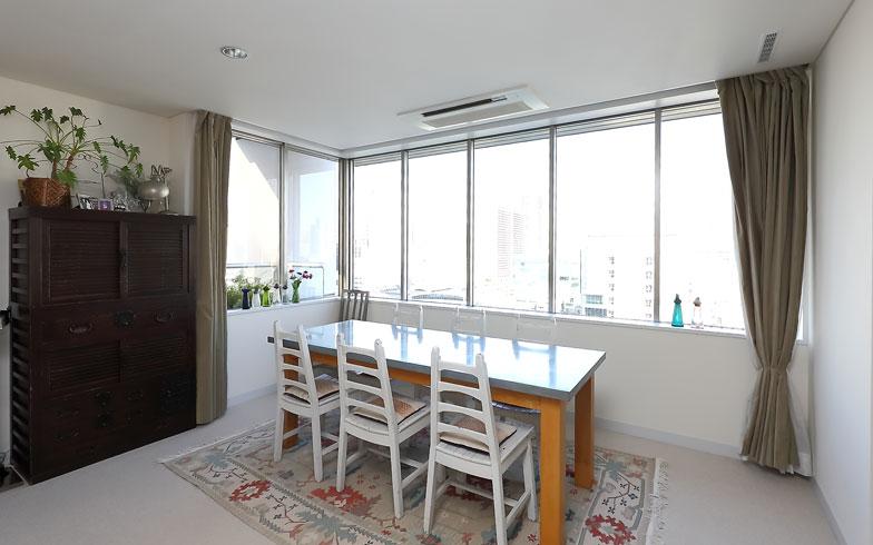 【画像1】壁幅いっぱいの窓から光差す空間。白イスは個性的なデザインでお気に入り(写真:飯田照明)
