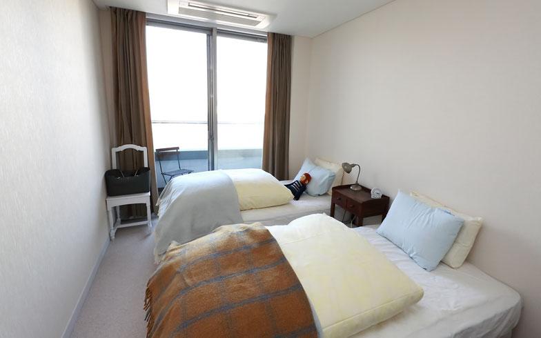 【画像11】ドイツ式ベッドメークですっきりまとめた寝室(写真:飯田照明)