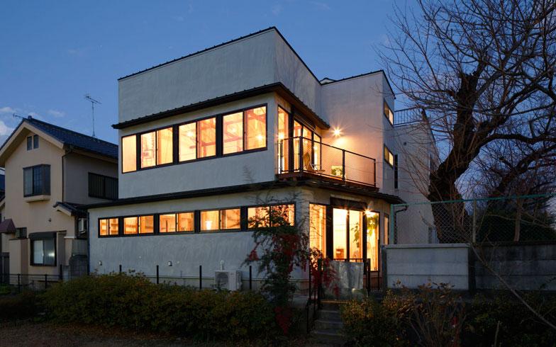 【画像2】「世田谷桜丘の家」夜景。1階は周辺からの視線に配慮して高い位置に、2階は大きめの開口部が連窓とされ、モダンな雰囲気だ(写真:リビタ)
