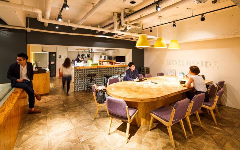 【画像1】半楕円のテーブルがあるダイニングスペース。キッチンとの間にあるカウンターにはスツールを置き、奥で料理をする人とも会話が楽しめるように工夫している(写真撮影/上條泰山)
