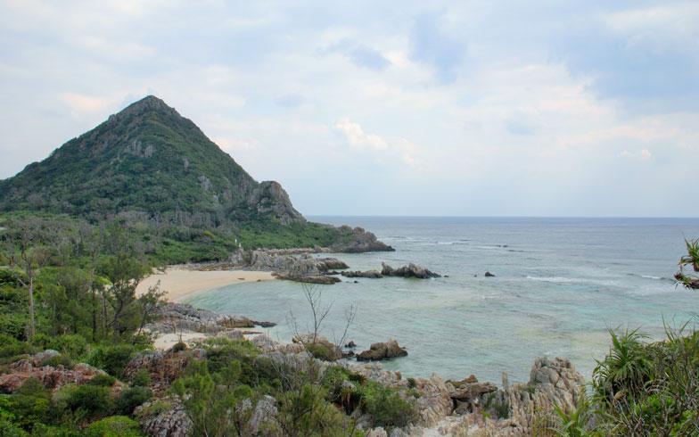 【画像2】伊是名島に近づくと三角錐のような山が見えてくる。伊是名グスク跡だ。手前に広がるのは、日本の渚100選に選ばれた「伊是名二見ヶ浦海岸」(写真撮影:伊藤加奈子)