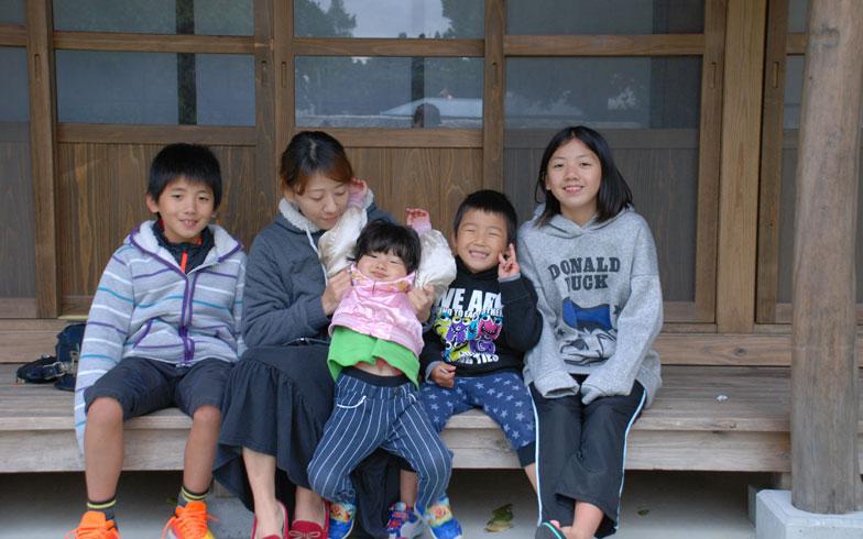 【画像3】移住した古民家の縁側に学校から帰った子どもたちが集合。右から長女(12歳)、三男(5歳)、四男(3歳)、伊藤さん(30代)、次男(9歳)の大家族。長男(10歳)は恥ずかしがり屋で、撮影にも飽きてしまい、どこかへ行ってしまった(写真撮影:伊藤加奈子)