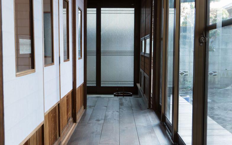 【画像2】コストダウンの工夫満載の玄関ホール。床材はアンティーク加工した無垢のボルドーパインで新品ながら古民家の雰囲気に合うように、サッシは既存の枠を生かして複層ガラスに変更。木の建具は元の家にあったものと施主支給したもの融合。縁側は既存を塗装してそのまま利用(写真撮影/片山貴博)