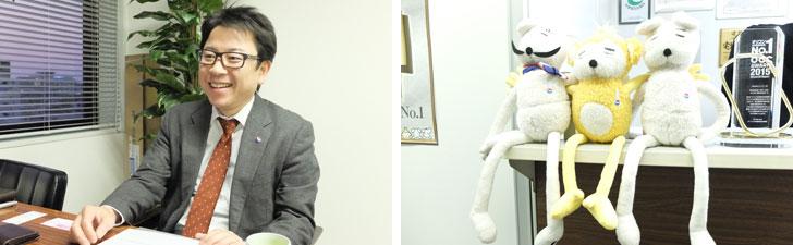 【画像1】左:ニッショー.jp代表取締役社長の加治佐弘さん。右:人気キャラクターが受付に。向かって左が「ミツケール」で右が「サガッシー」。中央は楽しいお部屋を「ツクルーノ」というサルで、2015年より登場(写真撮影:倉畑桐子)