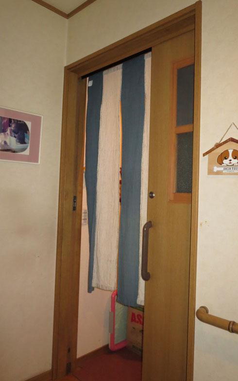 【画像5】広い廊下からバリアフリーでつながる引戸の玄関。壁には先代の愛犬の写真(写真撮影:藤井繁子)