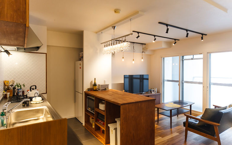 【画像4】対面カウンターの下部収納は両側から出し入れ可能。キッチン側にはダストボックスやキッチン家電を収納。キッチンの床はタイルを採用した(写真撮影/難波明彦)