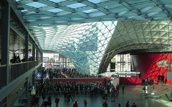 【画像1】イタリア人建築家マッシミリアーノ&ドリアナ・フクサスが2005年にデザインした会場、巨大なガラスのキャノピーに覆われている。こちらは南口ゲートで開場を待つ列(写真撮影/藤井繁子)
