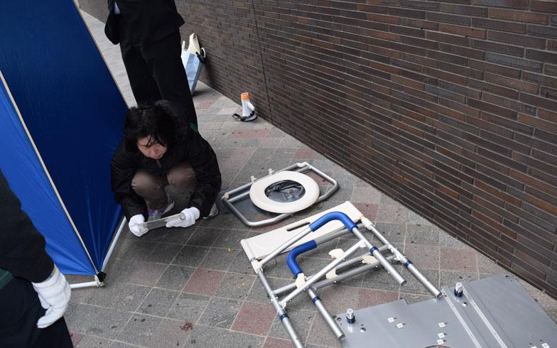 【画像7】こちらは、マンホールトイレの組み立て訓練。災害が起きたときにはマンションの敷地内にある「おすい」と書かれたマンホールを開けて、その上に置くことになる。説明書を解読しながら居住者同士で協力し、組み立てていく(写真撮影/末吉陽子)