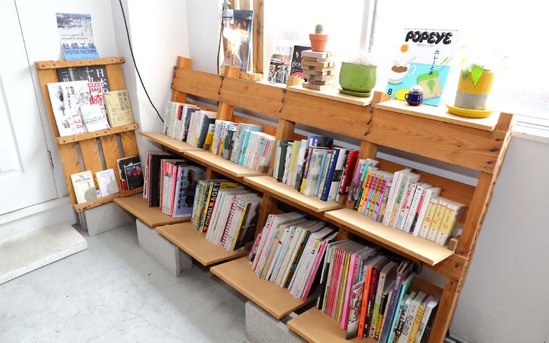 【画像3】以前の入居者が調達してきたという物流用木製パレット(すのこのようなもの)を利用し、DIYが得意な入居者が中心となって製作された共有スペースの本棚(写真撮影:飯田照明)