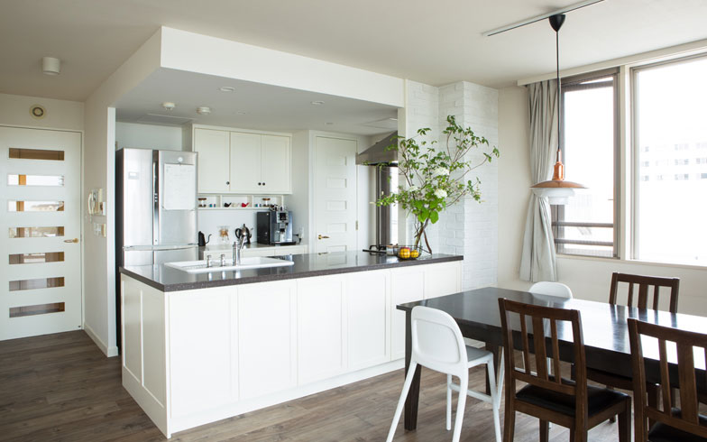【画像3】キッチンのアフター。キッチン上部にあった吊り戸棚を撤去し、造作カウンターを大きく。既存の床に二重貼りをしたほか、壁にもホワイト・ブリックをあしらった(撮影:片山貴博)