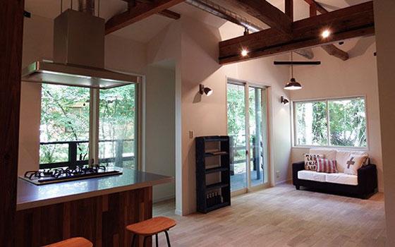 【画像1】和室のあった築35年の別荘は、リノベーション専門の「空間社」とのコラボにより、アイランドキッチンのある1LDKの別荘に。梁を見せた吹抜けの天井部分が開放的。価格は土地+建物で2550万円。築35年、建物面積52.13m2の中古別荘が間取りや外観もガラリと変え、新築別荘より安く販売されている(写真提供:富士急行)