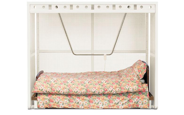 【画像1】ベッド型シェルター(税込54万円)。ベッドや布団を中に敷くことができるこちらの製品は、約10トンまでの耐圧性能があるため、就寝時や寝たきりの場合も地震による家屋倒壊から身を守ってくれる。衝撃を吸収するため穴が開いたスチール板を使用。低重心設計のため、巨大地震でもまず倒れることはないとか。特許を取得しており、各自治体で10万円から50万円の補助金の対象商品になっている(写真提供/エヌ・アイ・ピー)