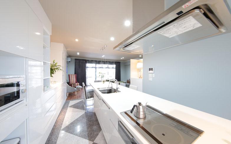 【画像6】キッチン奥からリビング方向を望む。床材をキッチンとリビングで分け、空間を緩く区切る(写真撮影/本美安浩)