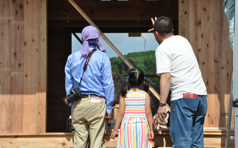 【画像4】地元の親子が安藤さんに説明を受けている。楽しそうに建物をつくっていると、人が集まってくるのが興味深い(写真撮影/嘉屋恭子)